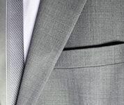 オーダースーツのポケットに手を入れる男性