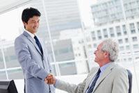 重役と握手をするスーツの男性