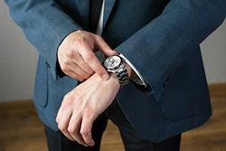 時計を確認するスーツの男性