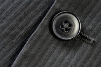 黒スーツに留められたボタン