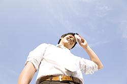 夏の炎天下の屋外で額の汗をぬぐう男性