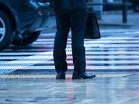 梅雨に横断歩道に立つスーツの男性