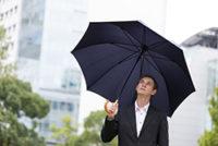 梅雨に傘を差すスーツの男性
