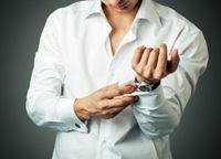 スーツの袖ボタンを留める男性