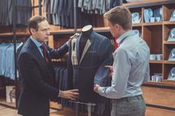オーダースーツを仕立てる店員と男性客