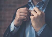 ストライプのYシャツのボタンを留める男性