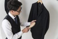スーツをブラッシングしている男性