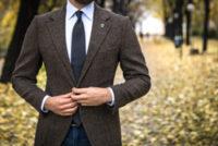 並木道に立つブラウンのスーツを着た男性