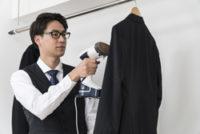 スチームアイロンでスーツのシワを取る男性