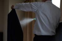 スーツに消臭スプレーをかけるビジネスマン