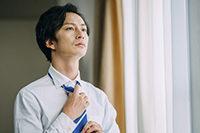 ネクタイを結ぶ男性