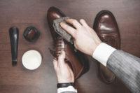 革靴のケアをする男性