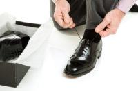革靴の靴ひもを結ぶ男性